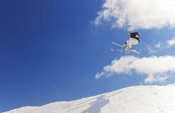 跳跃高在山的男性滑雪者 免版税库存照片