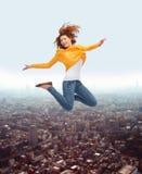 跳跃高在空气的微笑的少妇 免版税库存图片