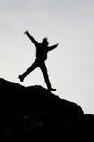 跳跃从与开放胳膊的一个岩石的男孩的黑剪影 库存图片
