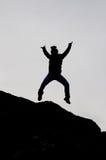 跳跃从与开放胳膊的一个岩石的男孩的黑剪影 免版税库存图片