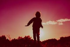 跳跃从在日落自然的喜悦的小男孩 免版税库存图片