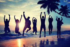 跳跃以在海滩的兴奋的剪影人 免版税库存照片