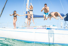 跳跃从小船的小组朋友 免版税库存图片