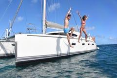 跳跃从小船的快乐的夫妇到海 免版税库存照片