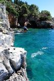跳跃从峭壁在海洋 库存照片