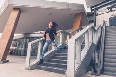 跳跃从楼梯的美丽的女孩 免版税库存图片