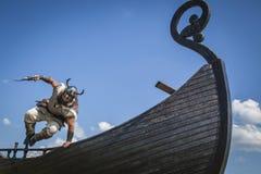 跳跃从他的船的坚强的北欧海盗到攻击 免版税图库摄影