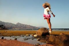 跳跃从石头的小女孩 免版税库存照片