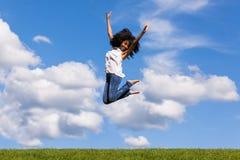 跳跃o的一个少年黑人女孩的室外画象 免版税库存照片