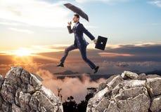 跳过与伞的峭壁的商人 库存照片