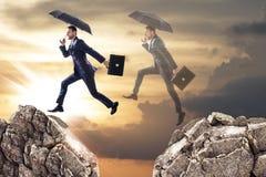 跳过与伞的峭壁的商人 免版税库存图片