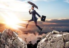 跳过与伞的峭壁的商人 免版税图库摄影
