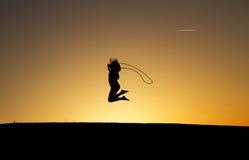跳过在日落的现出轮廓的女孩绳索 库存照片