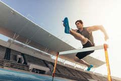 跳过在连续轨道的一个障碍的运动员 免版税库存图片