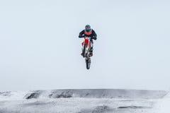 跳过山的摩托车越野赛车手 免版税库存照片