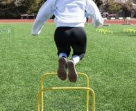 跳过微型障碍的高中女运动员在实践 免版税库存照片