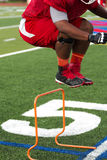跳过橙色障碍的架线工在橄榄球实践 免版税库存图片