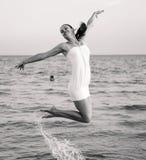 跳过海的愉快的深色的女孩 风格化作为减速火箭的照片 免版税库存图片
