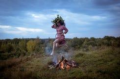 跳过火的北欧海盗年龄的斯拉夫的服装的女孩 免版税库存照片