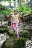 跳过石头的无所畏惧的小女孩侦察员 免版税图库摄影