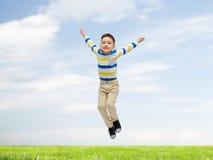 跳过蓝天和草的愉快的小男孩 库存图片