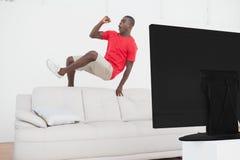 跳过长沙发欢呼的足球迷 免版税库存图片