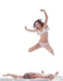 跳进与性感的人的床的快乐的亭亭玉立的妇女 图库摄影