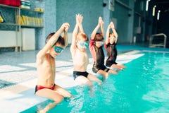跳进体育游泳池的孩子 免版税库存照片