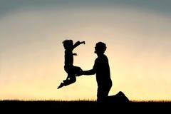 跳进愉快的父亲的胳膊的孩子剪影 免版税库存图片