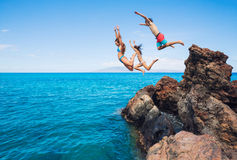 跳进海洋的朋友峭壁 库存照片