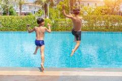 跳进游泳场、夏天休假和假期概念的两个小男孩乐趣 图库摄影