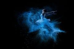 跳进蓝色粉末云彩的年轻美丽的舞蹈家 免版税库存图片