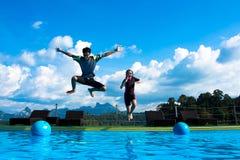 跳进水池的男孩和女孩在湖 免版税库存照片