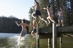 跳进从跳船的小组青年人湖 库存照片