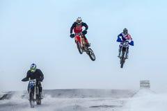 跳高和飞行车手在摩托车在冬天摩托车越野赛 免版税库存图片