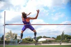 跳高运动员,当他跳时 r 库存照片