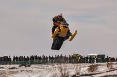跳高雪上电车的运动员 免版税库存图片