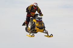 跳高雪上电车的运动员 免版税图库摄影