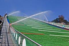 跳高滑雪小山的绿色塑料外壳在鲁斯基高尔基跳跃的中心在夏天维护下用冲洗的水 浇灌 库存照片