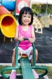 跷跷板的亚裔中国小女孩在操场 图库摄影