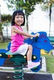 跷跷板的亚裔中国小女孩在操场 免版税库存照片