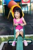 跷跷板的亚裔中国小女孩在操场 免版税图库摄影
