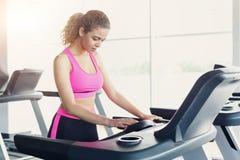 踏车的可爱的妇女在健身俱乐部,健康生活方式 免版税库存照片