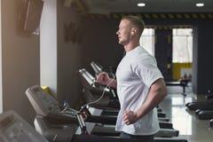 踏车的年轻运动的人在健身俱乐部 免版税库存图片