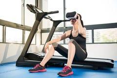 踏车的秀丽亚洲妇女基于有VR耳机的 库存照片