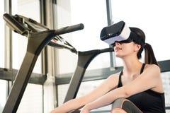 踏车的秀丽亚洲妇女基于有VR耳机的 免版税库存照片