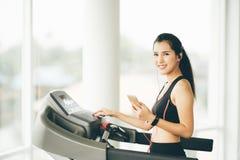 踏车的逗人喜爱的亚裔女孩在健身房听到在智能手机的音乐的通过体育耳机 库存图片