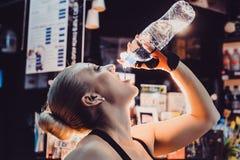 踏车饮用水的妇女,当行使在健身房时 库存图片