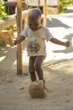 踢与一个残破的球的马达加斯加人的男孩足球 库存图片