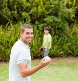 踢与他的父亲的儿子橄榄球 库存照片